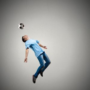Man in casual kick football ball over head